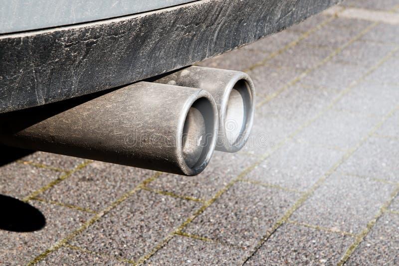 Les doubles pots d'échappement sales d'une voiture, émissions examinent image stock