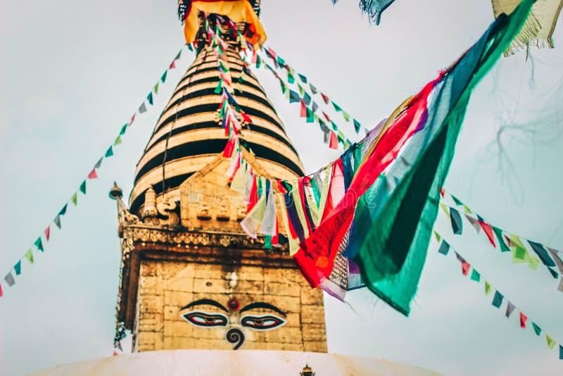 Les drapeaux bouddhistes de prière ont accroché sur une corde attachée à un dôme de temple photos libres de droits