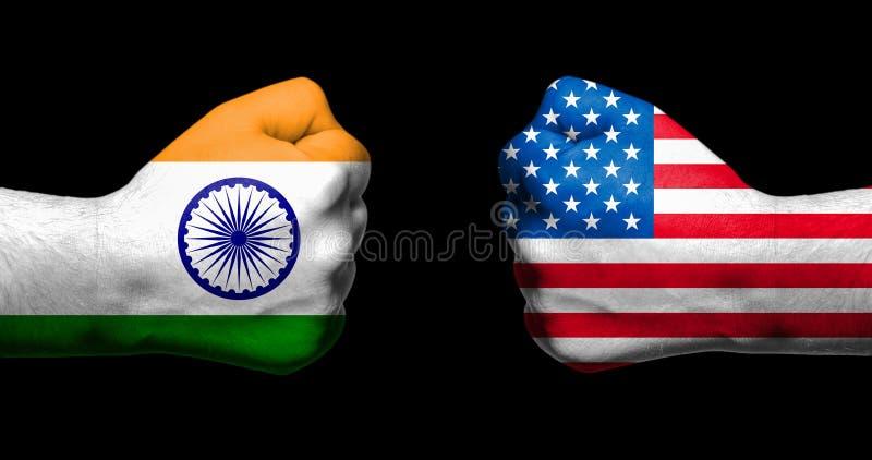 Les drapeaux de l'Inde et des Etats-Unis peints sur deux ont serré des poings se faisant face sur le fond/Inde noirs - le conflit images libres de droits