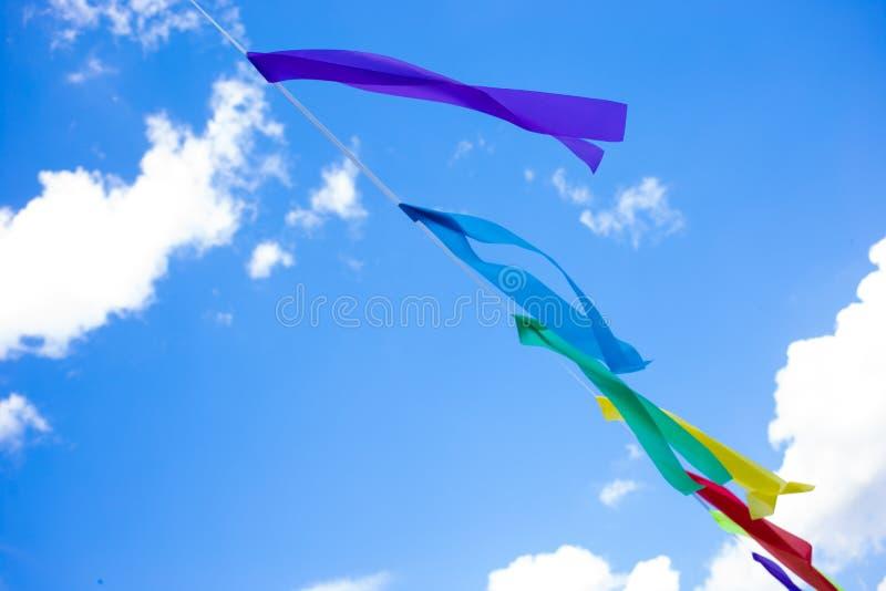 Les drapeaux de partie colorés célèbrent le résumé sur le fond de ciel bleu photographie stock libre de droits