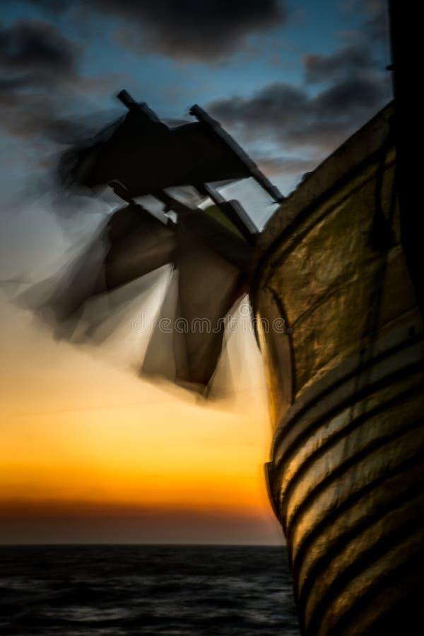 Les drapeaux de pot soufflent dans le vent sur un bateau de pêche à l'aube photographie stock libre de droits