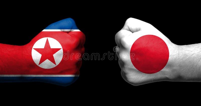 Les drapeaux du Japon et de la Corée du Nord peints sur deux ont serré le fac de poings image libre de droits