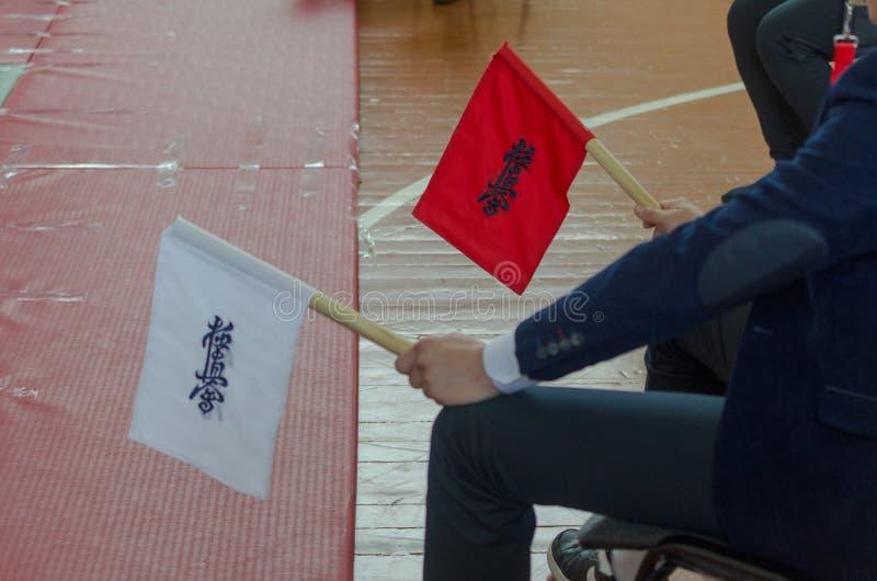 Les drapeaux rouges et blancs du juge en concours en arts martiaux aériens images stock