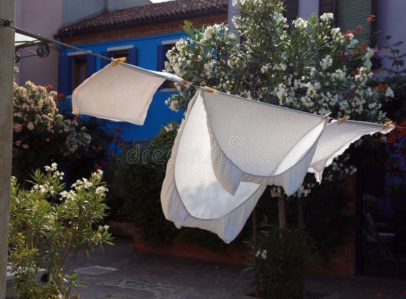 Les draps blancs ont écarté pour sécher au soleil dans un village photos libres de droits