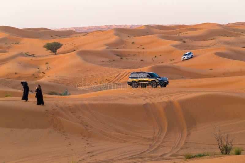 Les EAU Foudjairah 2017 19 11 deux femmes dans l'Arabe noir de l'orient vêtx la photographie Deux jeeps derrière eux images stock