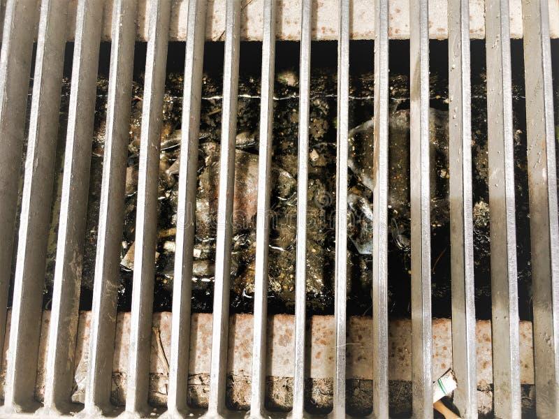 Les eaux d'égout de font pas la décharge dans des drains Les déchets en plastique obstruent des drains de précipitation exception image stock