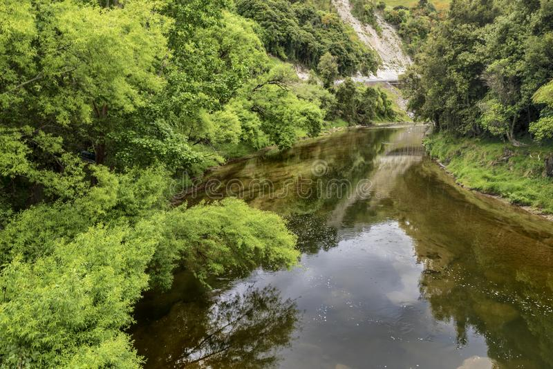 Les eaux toujours d'une rivière avec le feuillage luxuriant sur ses banques photo libre de droits