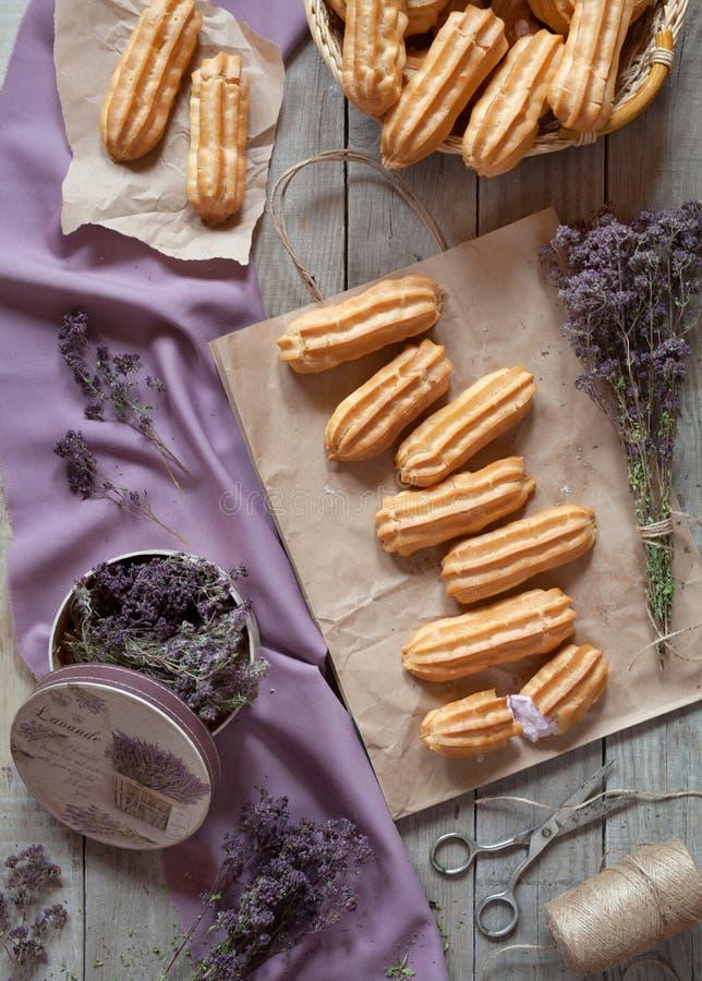 Les Eclairs ou le dessert de pâtisserie de profiterole ont rempli de crème fouettée image libre de droits