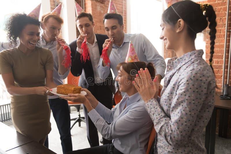 Les employés multiculturels dans des chapeaux de partie félicitent femelle avec le gâteau d'anniversaire photo stock