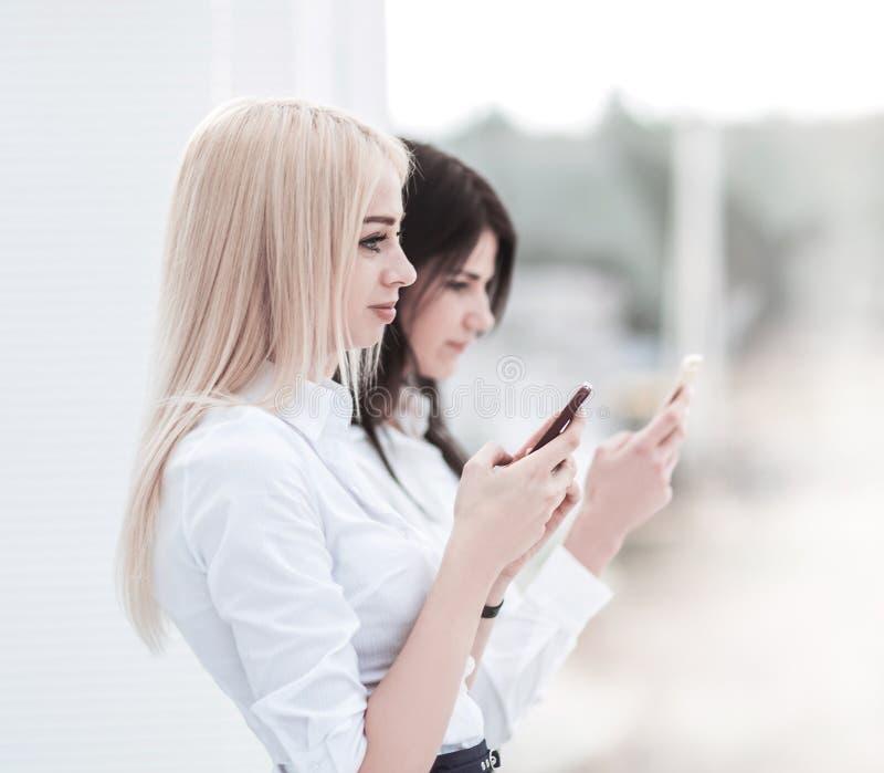 Les employ?es de jeunes femmes de la soci?t? ?changent l'information sur un smartphone image libre de droits