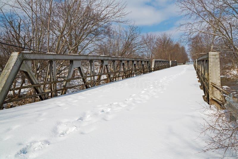 Les empreintes de pas croisent un vieux pont photos stock