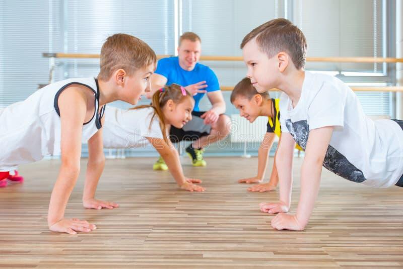 Les enfants à la leçon d'éducation physique dans le gymnaste de gymnase d'école badinent image libre de droits