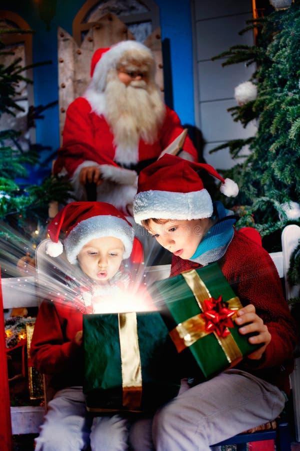 Les enfants étonnés ouvrent le cadeau magique de Noël image stock