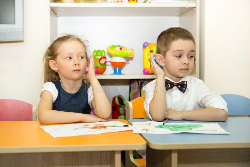 Les enfants adorables garçon et fille dessine une brosse et des peintures dans la chambre de crèche Enfant dans le jardin d'enfan photographie stock