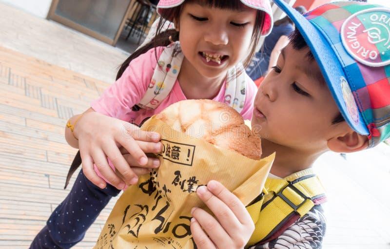 Les enfants asiatiques mange du pain célèbre du ` s Melonpan d'Asakusa photos libres de droits
