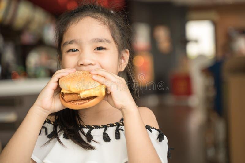 Les enfants asiatiques mangent l'espace restauration d'hamburger de fromage de poulet photo stock