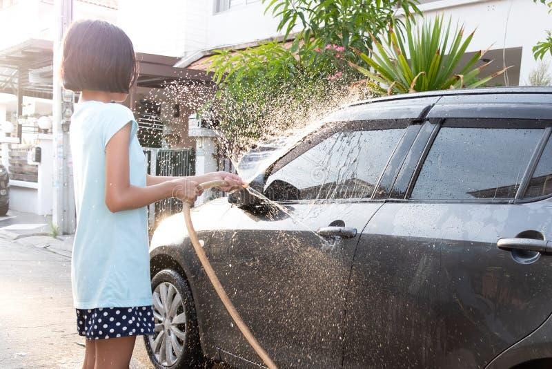 Les enfants asiatiques utilisent le tuyau de l'eau à la voiture de lavage photographie stock