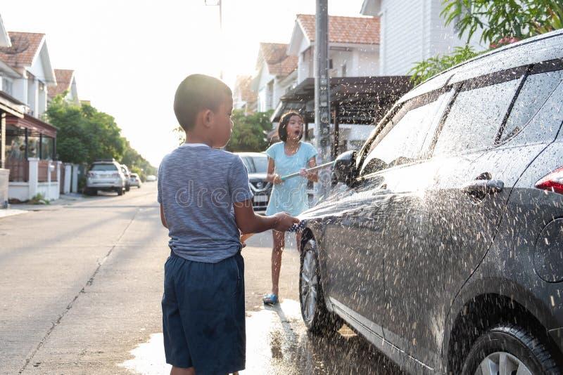Les enfants asiatiques utilisent le tuyau de l'eau à la voiture de lavage pendant le matin images libres de droits