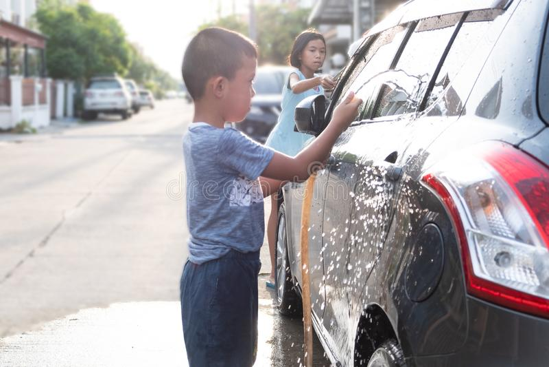 Les enfants asiatiques utilisent le tuyau de l'eau à la voiture de lavage photo libre de droits