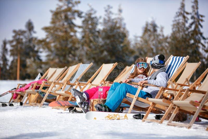 Les enfants aux montagnes en hiver riant et détendent dans le cha de lit pliant image stock