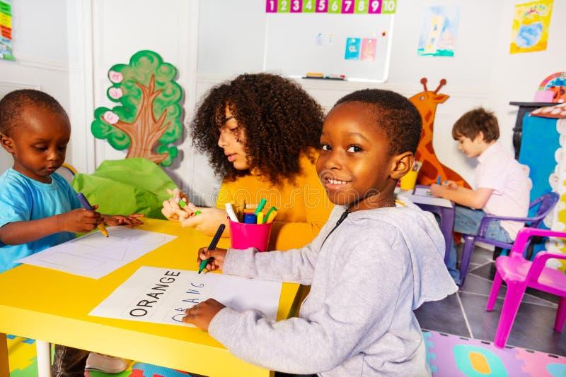 Les enfants avec le professeur apprennent à écrire des mots par un modèle images libres de droits