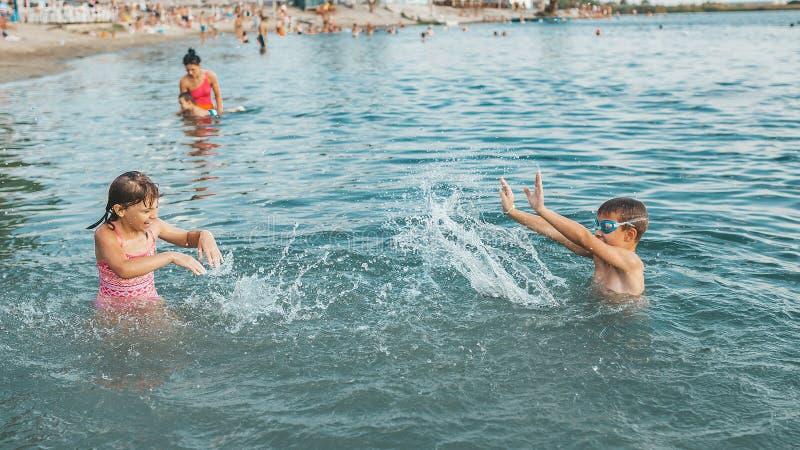 Les enfants ayant l'amusement avec éclabousse dans l'eau image libre de droits