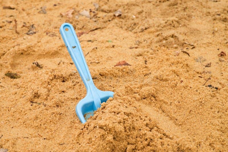 Les enfants bleus pellent le jouet sur le sable blanc, jeu en plastique pour le jeu Monticule du sable dans le jardin d'enfants images stock