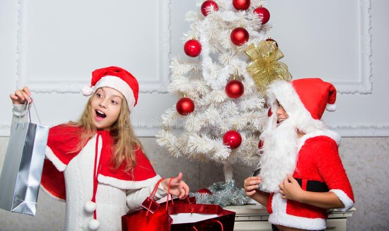 Les enfants célèbrent Noël avec des cadeaux L'enfant Santa de garçon avec la barbe artificielle blanche et le chapeau rouge donne images stock