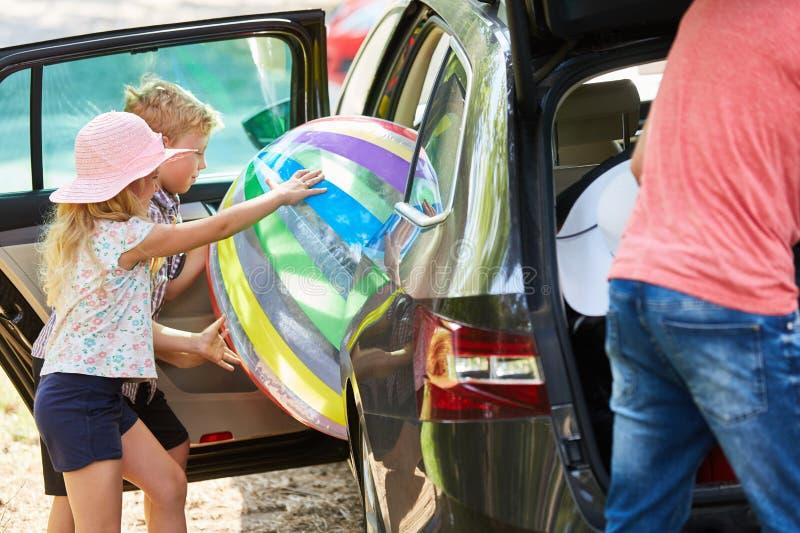 Les enfants chargent une grande boule dans la voiture photos stock