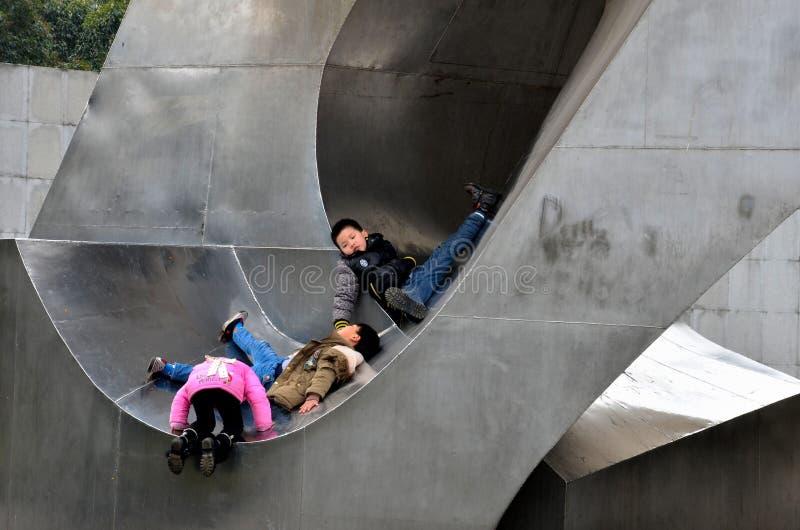 Les enfants chinois jouent dans la sculpture extérieure en métal, Changhaï Chine image libre de droits