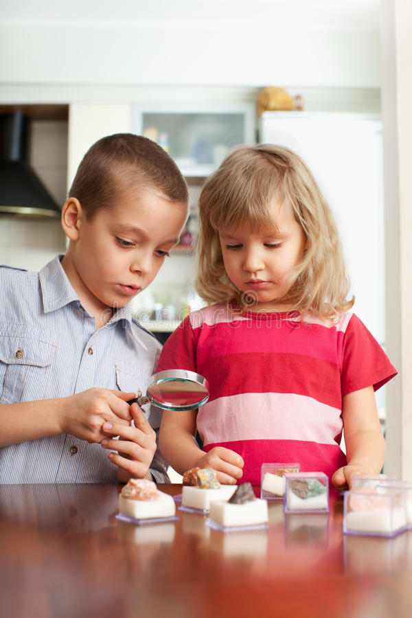 Les enfants considèrent une collection de loupe de pierres photographie stock