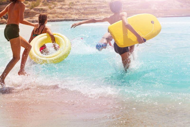 Les enfants courent et sautent dans l'eau sur la plage de sable image libre de droits