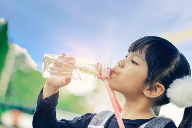 Les enfants d'école boivent l'eau d'une bouteille contre le ciel de fond images libres de droits