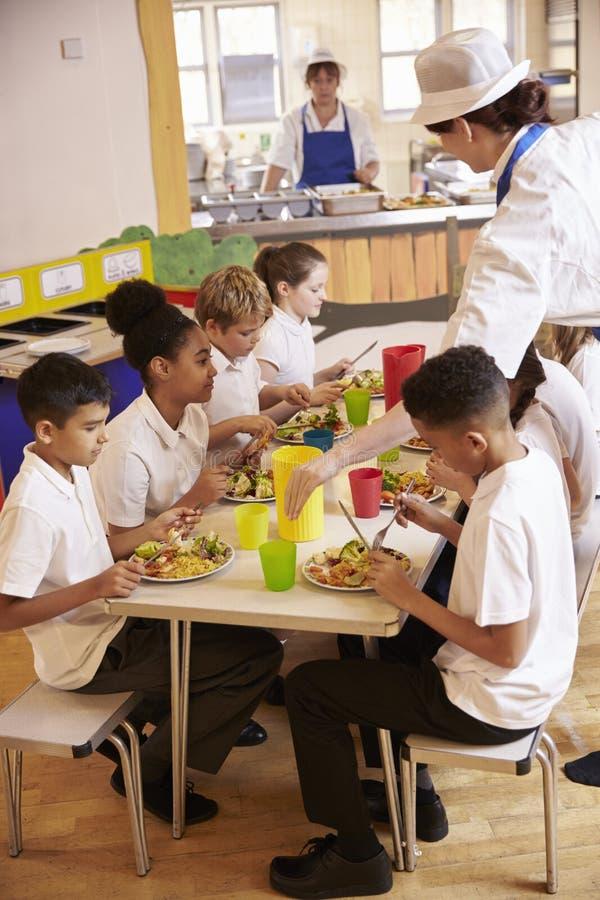 Les enfants d'école primaire mangent le déjeuner dans la cafétéria de l'école, verticale images stock