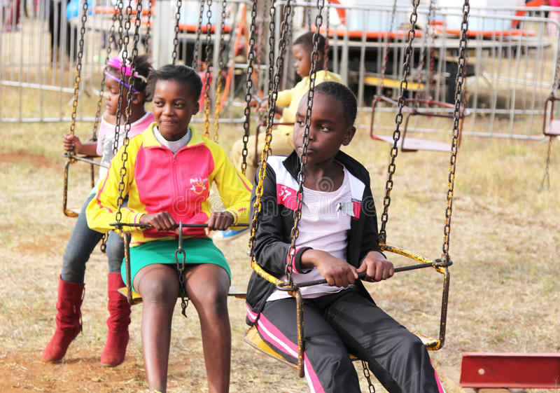 Les enfants d'africain noir attendant le rond point montent au début photos libres de droits