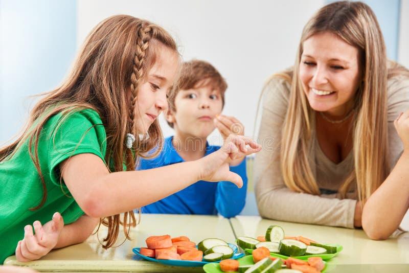 Les enfants dans l'école primaire mangent des légumes photographie stock libre de droits