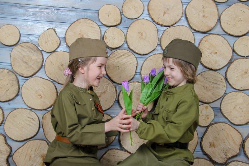 Les enfants dans l'uniforme en l'honneur de Victory Day dessus peuvent 9 se féliciter photos libres de droits