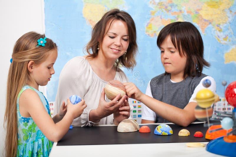Les enfants dans la classe élémentaire de la science étudient notre foyer o de système solaire image stock