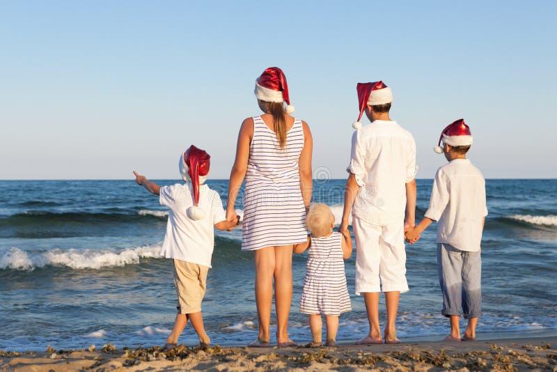 Les enfants dans le chapeau du père noël se tiennent sur la plage photo libre de droits