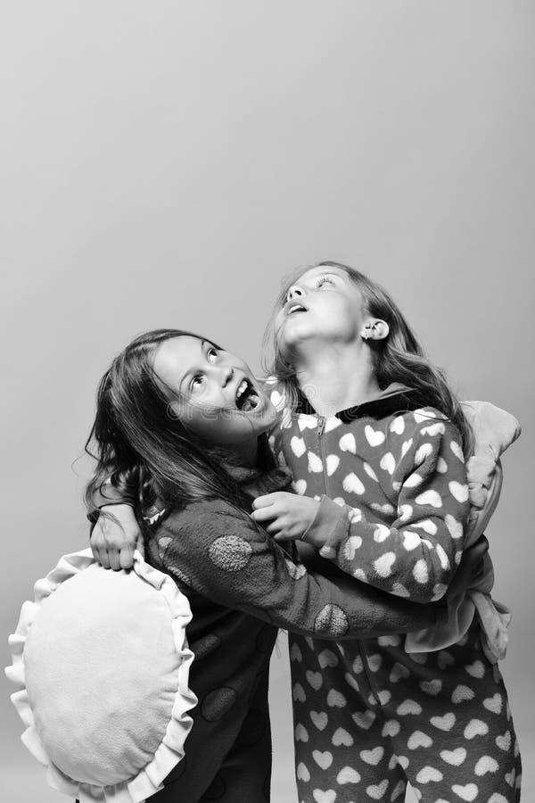 Les enfants de concept de partie et d'enfance de pyjama avec les visages étonnés tiennent les oreillers verts et jaunes image libre de droits