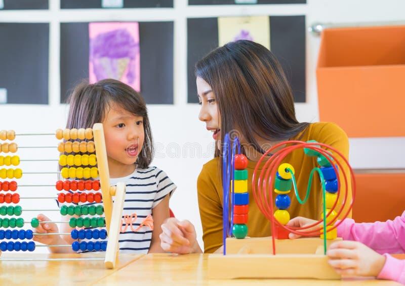 Les enfants de enseignement asiatiques de m?tis de professeur f?minin jouent le jouet dans la salle de classe, concept d'?cole de photos libres de droits