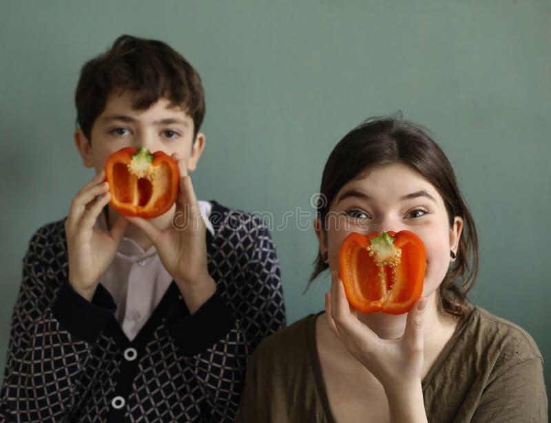 Les enfants de l'adolescence avec le bonbon rouge ont coupé le poivre bulgare de paprika photo stock