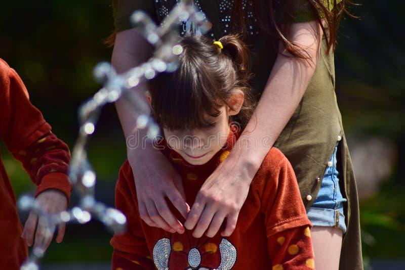 Les enfants de la même famille se tenant à la fontaine dans la ville se garent image stock