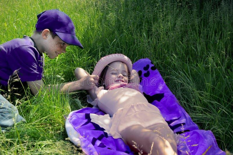 Les enfants de mêmes parents appréciant le soleil, le frère taquine sa petite soeur image stock