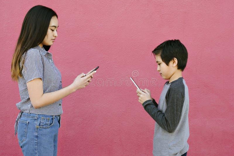 Les enfants de mêmes parents parlent entre eux utilisant leurs téléphones textotant la communication de temps modernes de concept image stock