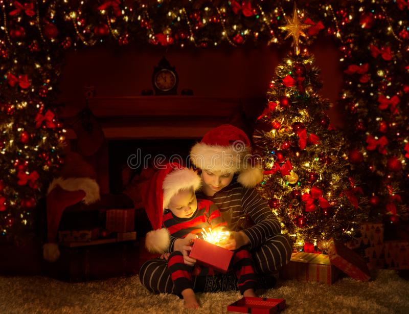 Les enfants de Noël ouvrent l'éclairage présente des cadeaux sous l'arbre de Noël, des bébés garçons en chapeau rouge, une scène  photos libres de droits