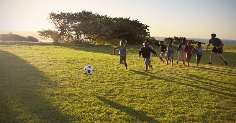 Les enfants de professeur et d'école primaire jouent au football dans un domaine photos stock