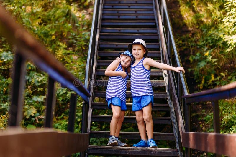 Les enfants de sourire dans les T-shirts rayés, les shorts bleus et des chapeaux se tiennent étreignants sur les étapes en ét photo libre de droits