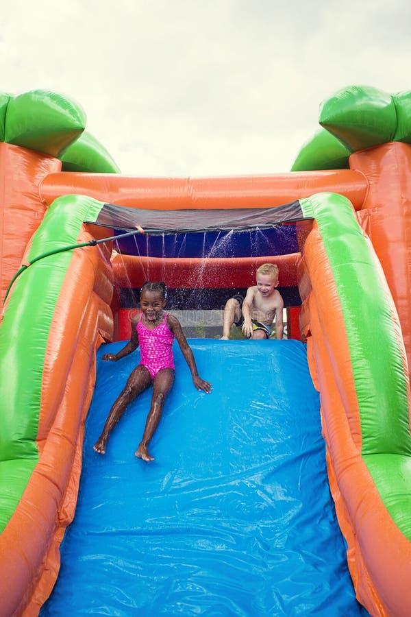 Les enfants de sourire heureux jouant sur une glissière gonflable rebondissent la maison image stock
