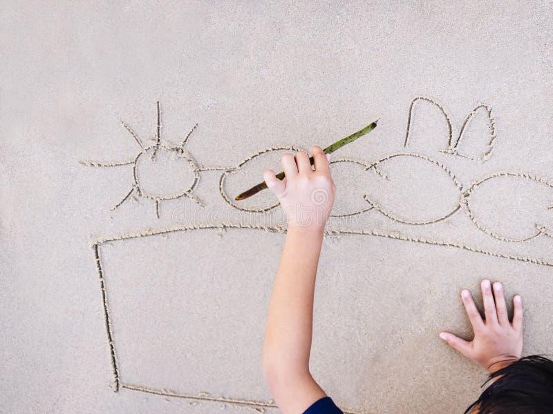 Les enfants dessine la photo sur le fond de vacances d'été de plage de sable images stock